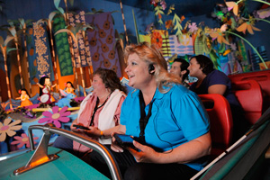 A female Guest enjoying It's a Small World ride with her family through an Assistive Listening device.