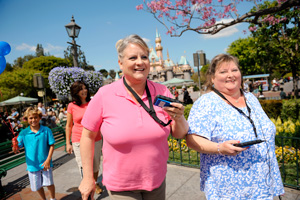 Two female Guests enjoying their day at Disneyland with Audio descirption devices with Sleeping Beauty's castle in the backround.