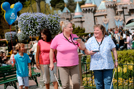 Two women smiling and enjoying their walk through the Disneyland resort holding a Sync Link device