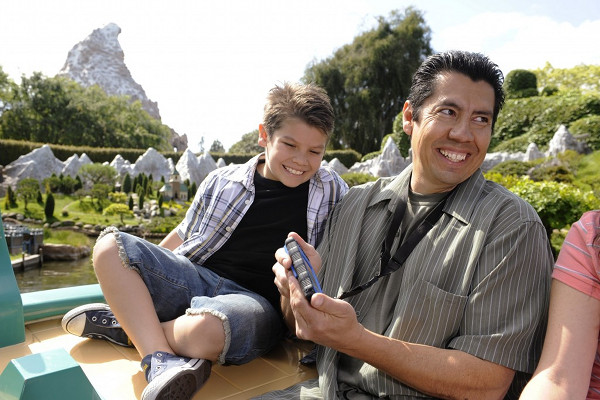 A father and son using the Sync Link technology to enjoy a descriptive ride through Storybook land.
