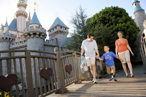 A father and mother walking their son with proesthic legs over a bridge with Sleeping Beauty\'s castle in the background.